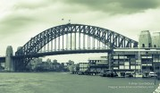 Sydney Harbor Bridge, Australia with darkening rain clouds gathering above split tone image green hue